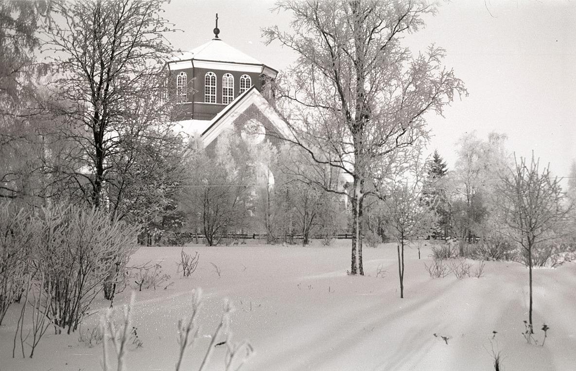 Kyrkan bakom björkarna som är täckta av rimfrost.