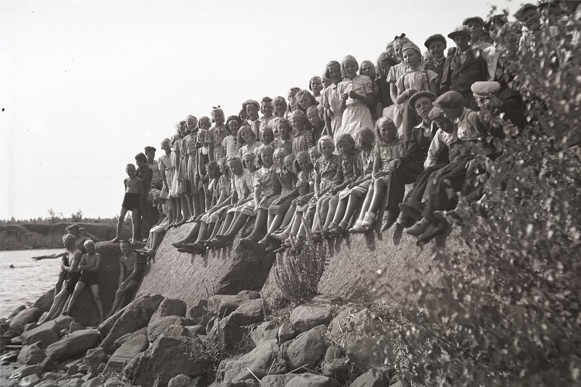 Klubbmedlemmarna sitter uppradade vid Härkmeri fjärden under utfärden 1941.