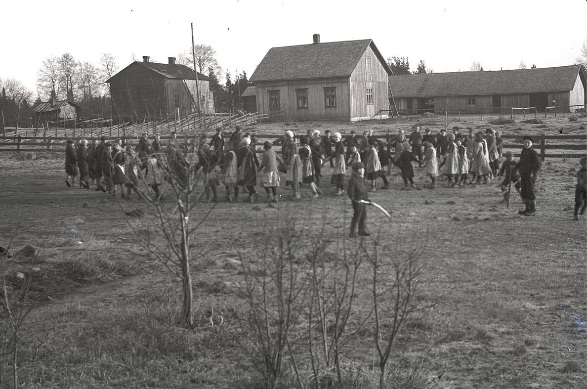 """Elevernas ringlekar på skolgården. Mitt i bild """"Gustas Kaalas"""" gård, alltså Artur och Hilma Ådjers gård. Till vänster står Arturs farmor Henrikas gård, där också Arturs faster Manda bodde.."""