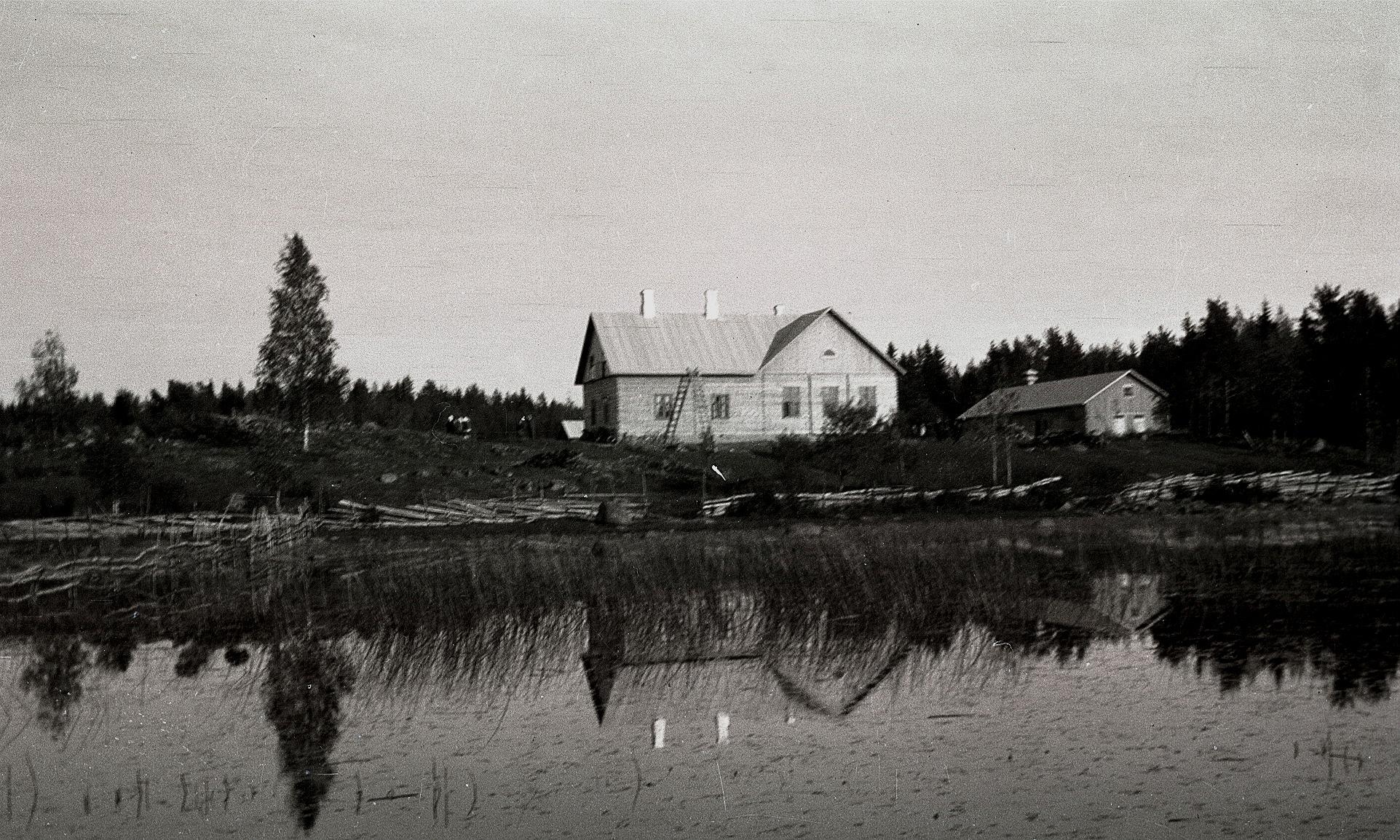 På stranden bortom Sindersjön står folkskolan i Träskvik.