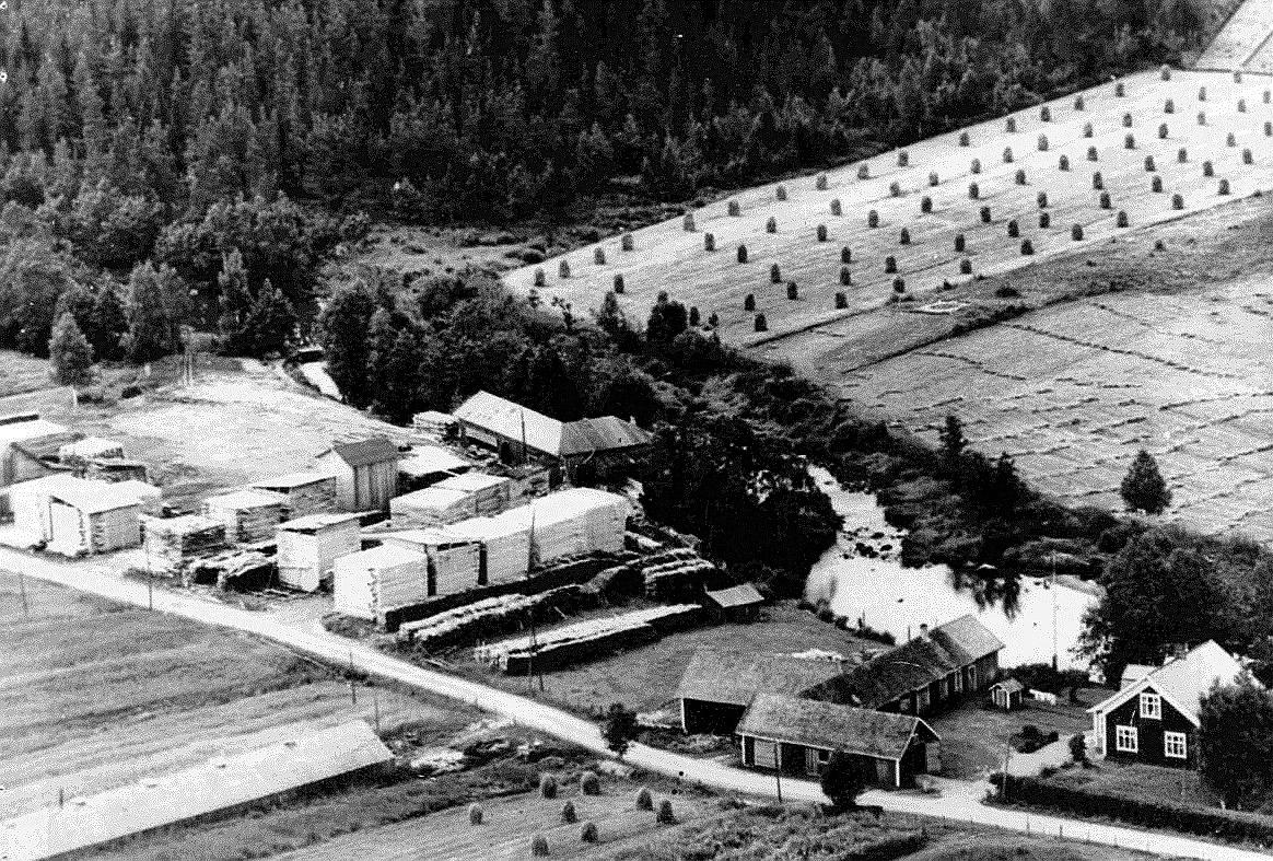 Flygfoto från tidigt 60-tal där Kvarnå Såg syns mitt i bild och sågägaren Emil Nyholm gård till höger. Själva sågbyggnaden byggdes i början på 1950-talet, då den gamla från 1930 revs.