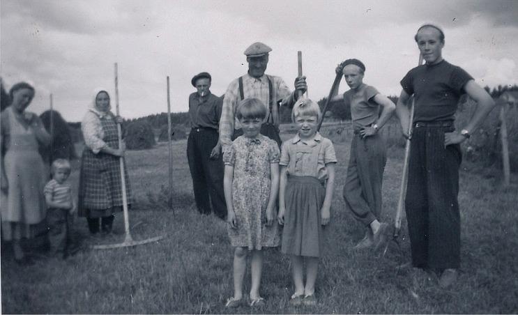 Höbärgningen förr var ett tidsödande arbete som hela familjen deltog i. Till vänster står Gerda Eskola med dottern Eila, Hulda håller i räfsan, Nils tänder sin tobak och Johan Viktor håller i högaffeln liksom sönerna Boris och Rune. Framför Johan Viktor står grannflickorna Inger och Solveig Dahlroos. Fotot från mitten på 1950-talet.