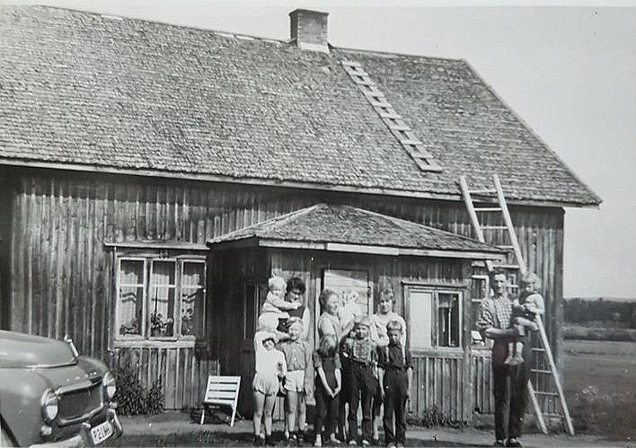 På fotot från mitten på 60-talet står Elisabeth Dahlroos, senare Svensson med dottern Helena i famnen. Fram henne står de andra barnen Gunilla och Magnus. Mitt i bild står Sylvia med Lasse i famnen och framför står Carola, Ole och Elof. Till höger Otto med Saga i famnen.