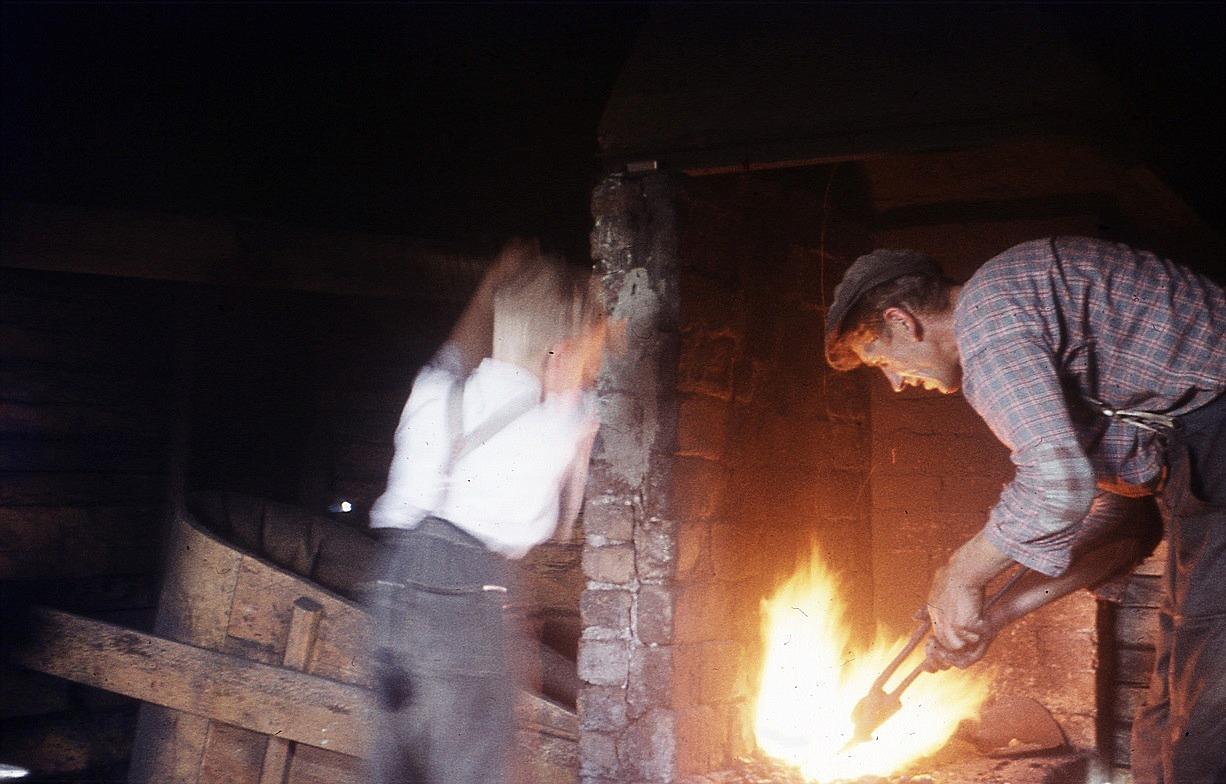På Nils Bergmans foto håller Otto järnet i ässjan med sonen Sixten hjälper till.