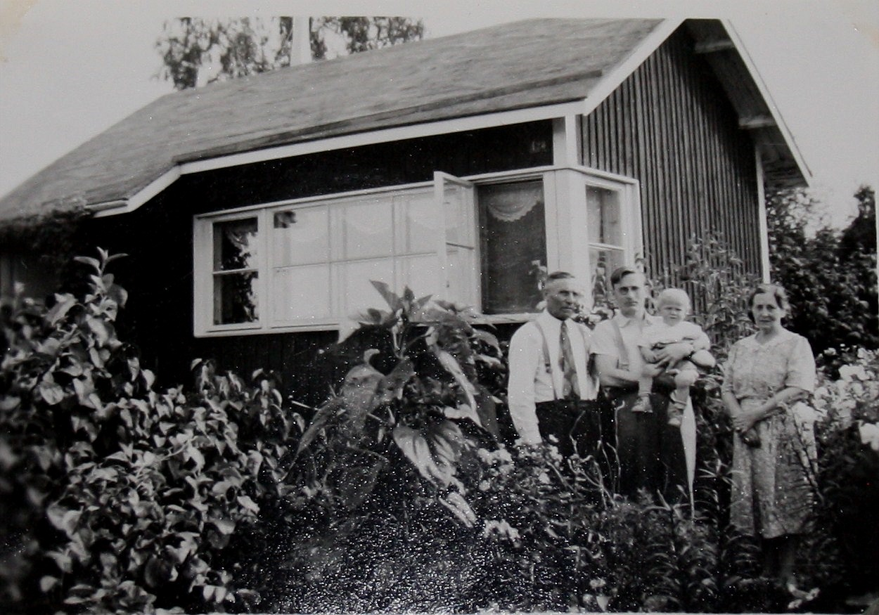 Här står Emil Båsk utanför kolonistugan tillsammans med Wilhelm med sonen Gustav i famnen, till höger står Ida Båsk.