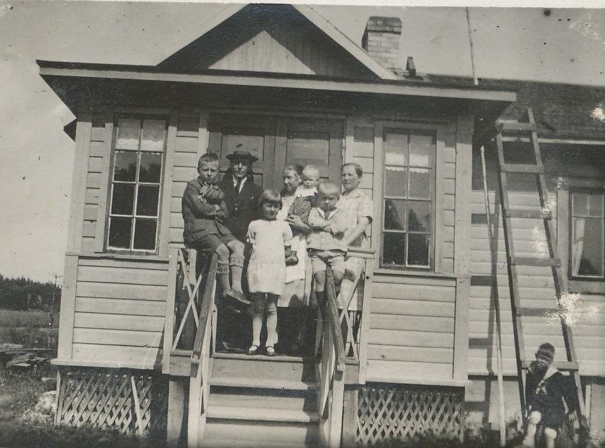 Här på trappan till huset i Åggelby står familjen Båsk. Längst bak står Anders med hustrun Selma som har yngsta dottern Margit i famnen. Från vänster barnen Arne, Gullborg och Nils. Kvinnan längst till höger borde vara Hulda Lindell.
