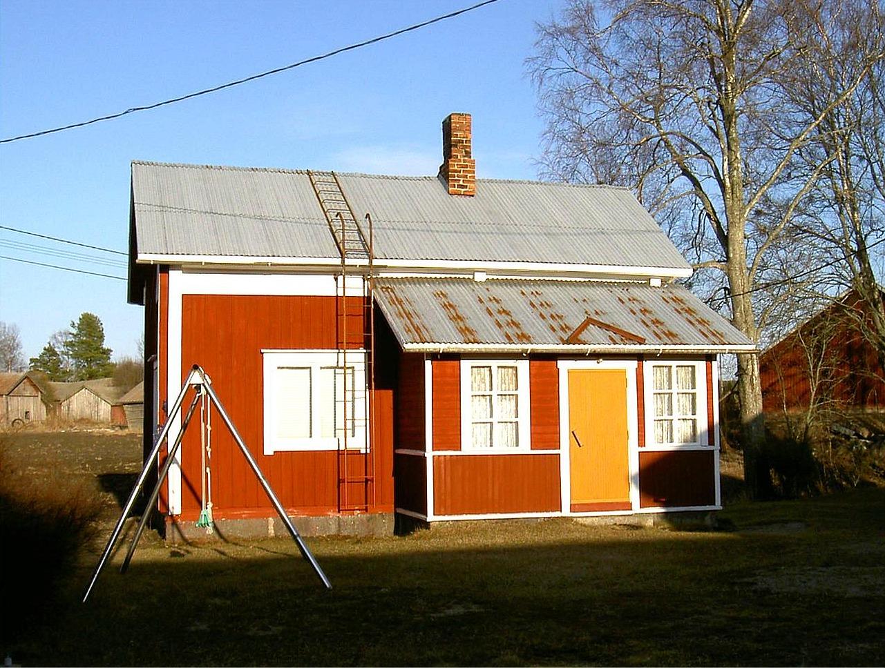"""Efter att Hilma Sandlund hade sålt hemmanet åt familjen Norrvik flyttade hon till lillstugan och hon bodde ensam där under en lång tid. Hilma dog år 2000 och hon var den sista som bodde i lillstugan. I vänstra kanten syns hennes barndomshem där """"Skomakas"""". Fotot från 2003."""