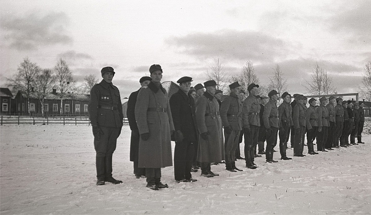 Skyddskårsmönstring på sportplanen i Lappfjärd. Till vänster Bertel Ekman som är dekorerad med flera medaljer och framför honom står Artur Björses.