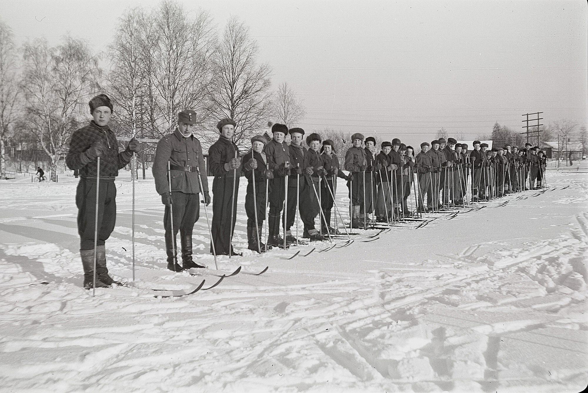 Soldatgossekåren uppställda med skidor på sportplanen. Till vänster Åke Ålgars och Torsten Mitts.