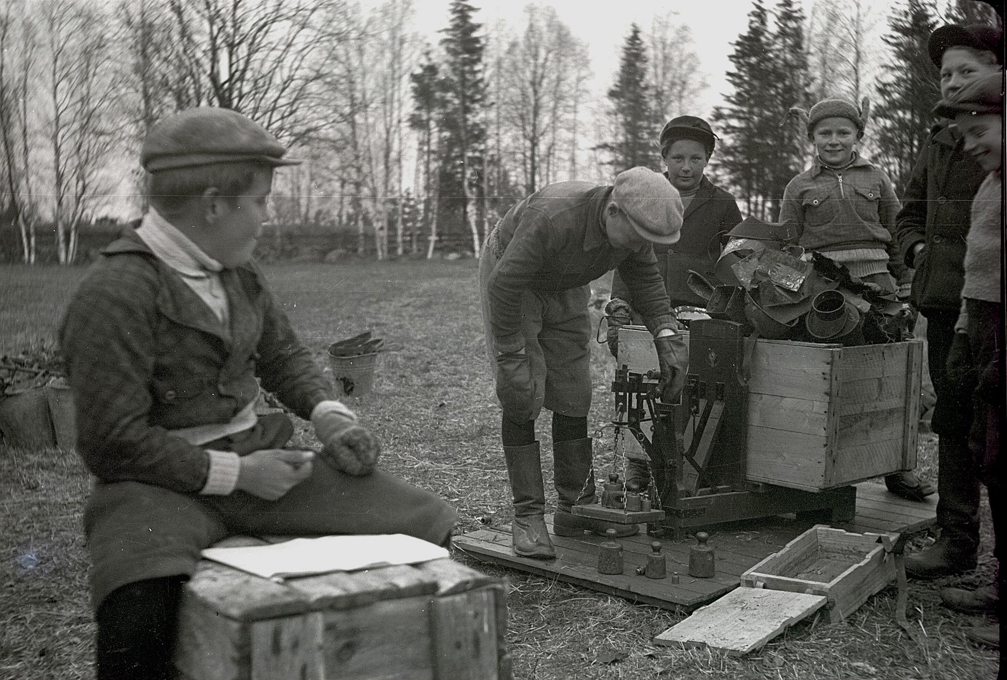 Metallerna som samlades in för försvarsmakten skulle vägas och bokföras. Runar Storsjö sköter bokföringen medan vägaren är okänd. Bakom står Erik Skogman och Fjalar Marttila.