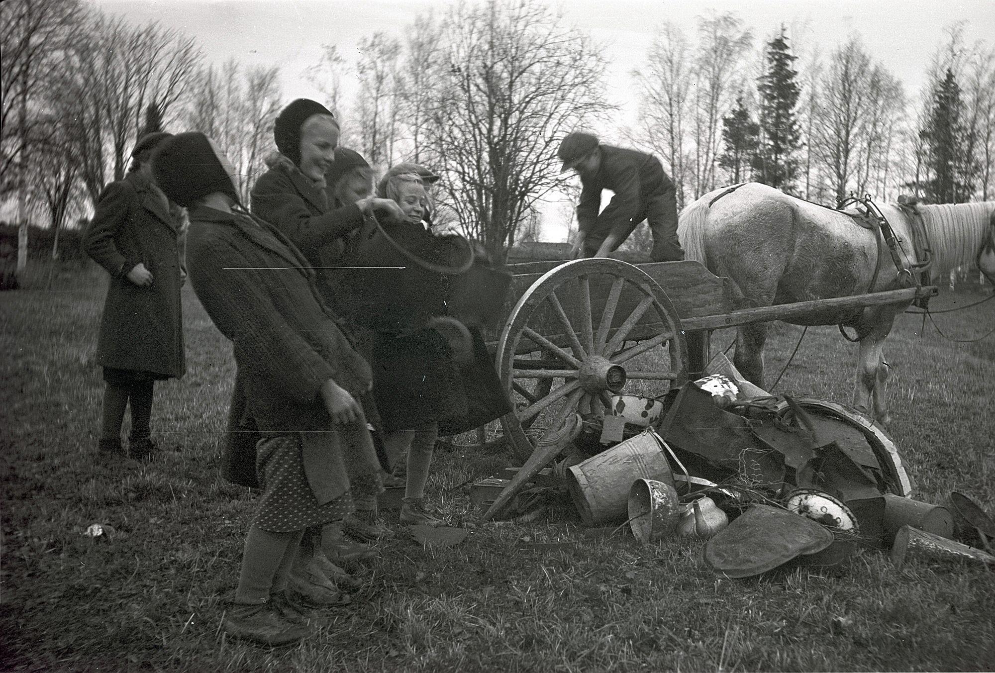 Under krigsåren 1941-44 samlade skolbarnen skrot för försvarsmakten. Pojken på kärran lastar av de insamlade metallerna medan flickorna ser på. Från vänster Etel Storsjö, Elvi Lassfolk, Ulla Sjöberg, okänd och Astrid Nissander.