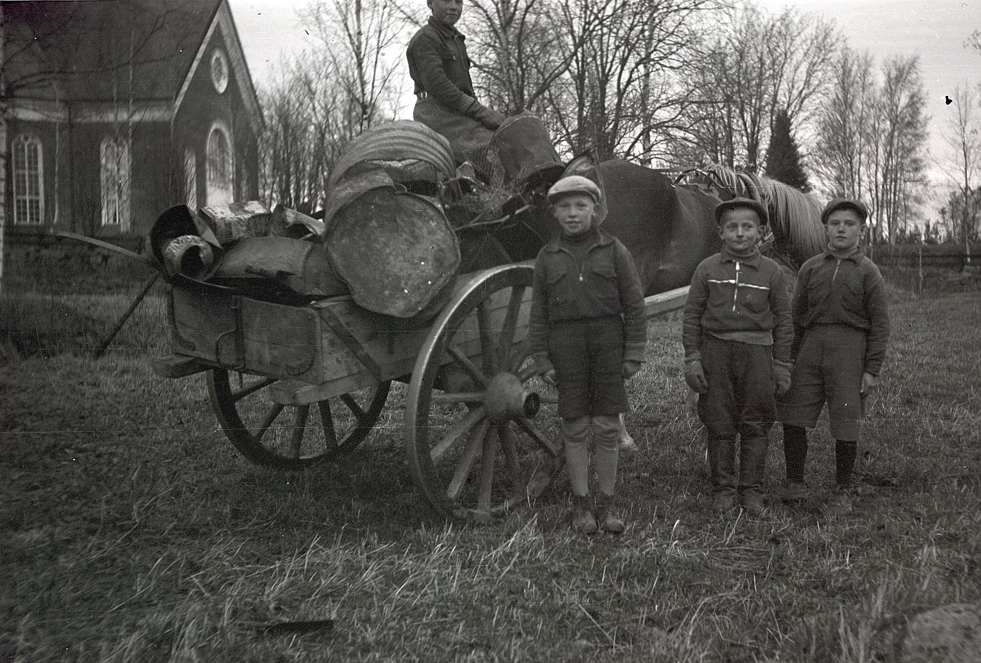 Under krigsåren samlades gummi, glas och metallskrot och här står 3 stolta pojkar som med häst levererar de insamlade metallerna. Från vänster Bengt Engelholm, Harald Marttila och Mikael Björses. Personen på kärran är oidentifierad.