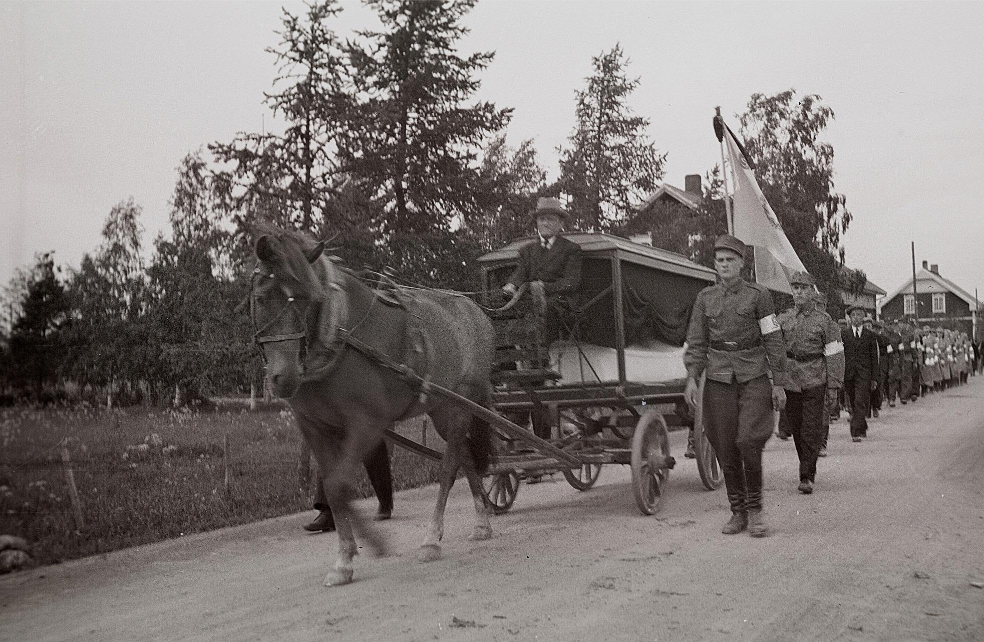 Viktor Ålgars kör sonen Eskil till den sista vilan i hjältegraven vid kyrkan, följd av lottor, skyddskårister och anhöriga. Bredvid Viktor går hedersvakten Erik Ingves.