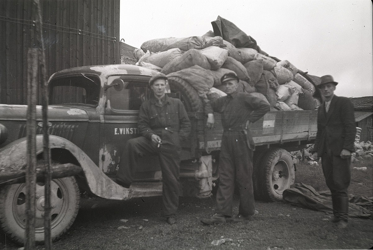 Konrad Kronman står till höger och granskar transporten av säckar som möjligtvis innehåller träkol.