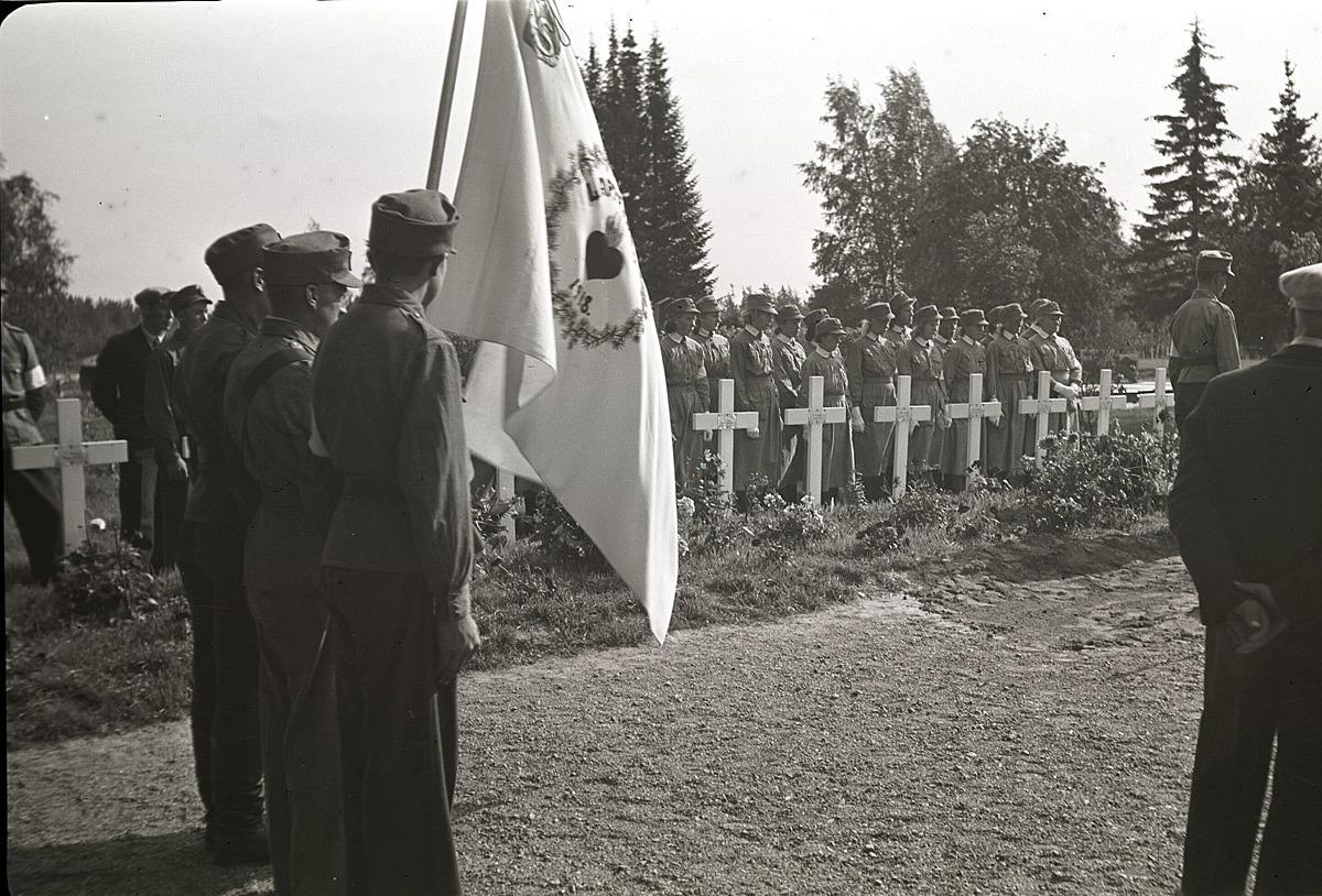 Skyddskårens fana vajar då Eskil Ålgars begravs på begravningsplatsen bredvid kyrkan i Lappfjärd.