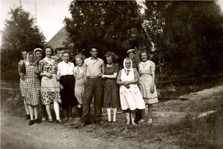 """Frida Klemets gifte sig i Frans Storkulls gård på midsommaren 1950 med Reino Rajala från Bötom, samma dag som Torsten gifte sig med Kaino i Bötom. Här är bekanta samlade till kockkalas dagen efter, från vänster: Gerda Storkull, """"Ottoas-Elin"""" Rosenback, Senja Puputti med dottern Anja som syns lite bakom Hjördis Skoglund som var kusin till Frida Klemets. Följande är Fridas mor """"Skräddarinas-Tilda"""" och bredvid henne står Elna Lindfors. Den långa mannen är Reino Rajala med hustrun Frida och bredvid Frida står """"Sanderas-Mina"""" Viiala från Palon och längst till höger står Fridas bror Nils och Helvi Klemets."""