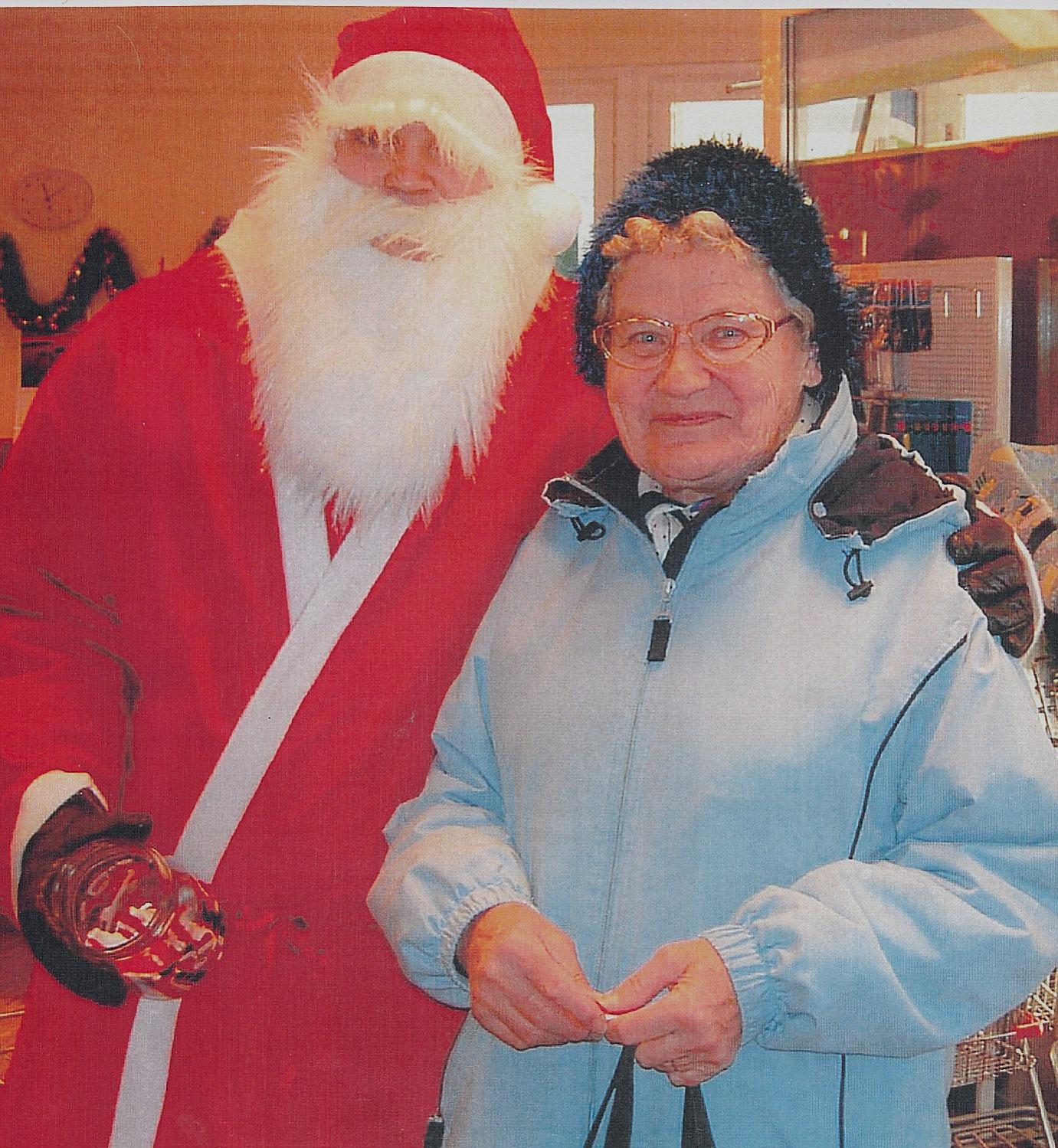Helvi Klemets ser nöjd ut då jultomten kramar om henne i bybutiken i Dagsmark