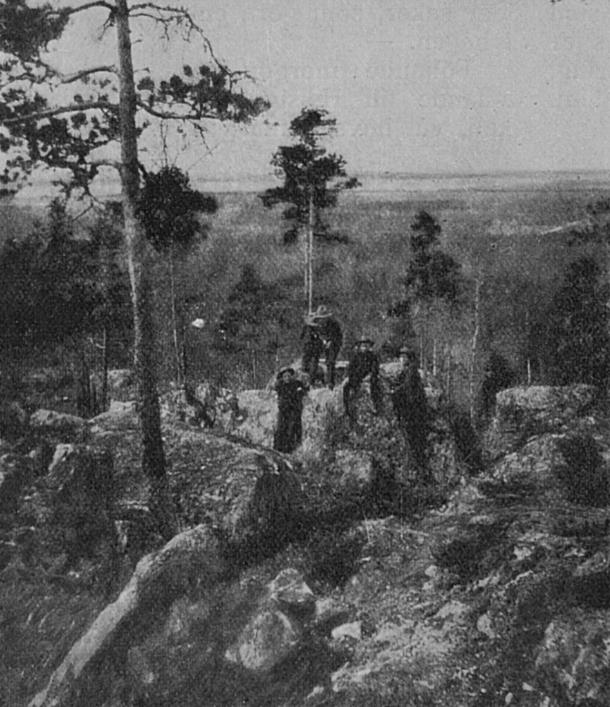 Bakom pojkarna finns Bastuväggen, en klippvägg som stupar snett inåt.