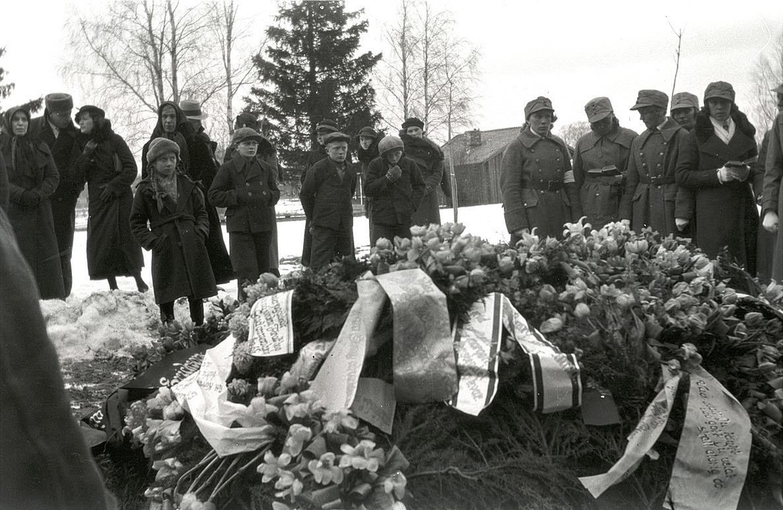 Kriget skördade offer hela tiden och här ser vi allvarstyngda miner runt en hjältegrav.