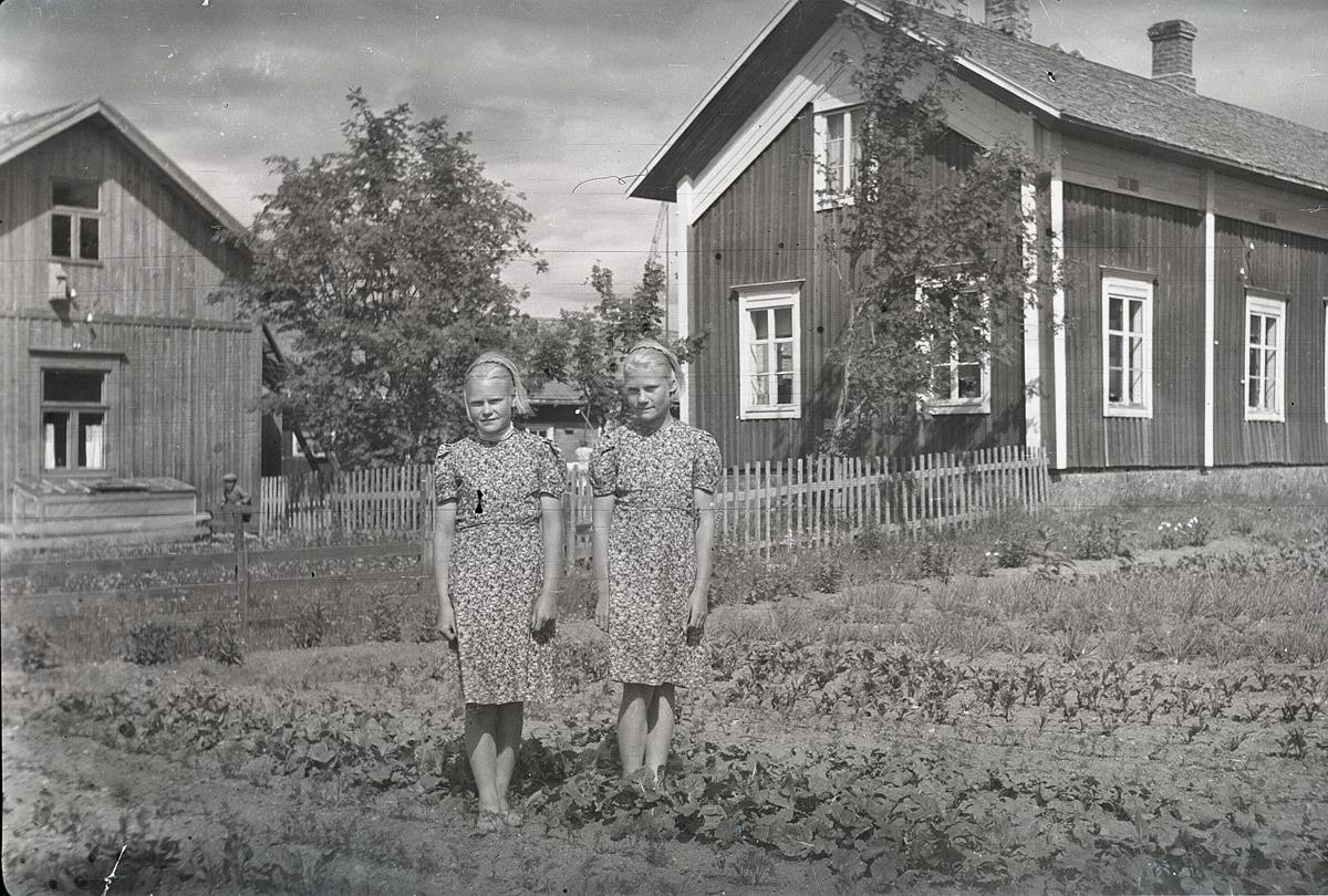 Systrarna Irma och Margit Rosendahl i trädgårdslandet framför hemgården i Lappfjärd.