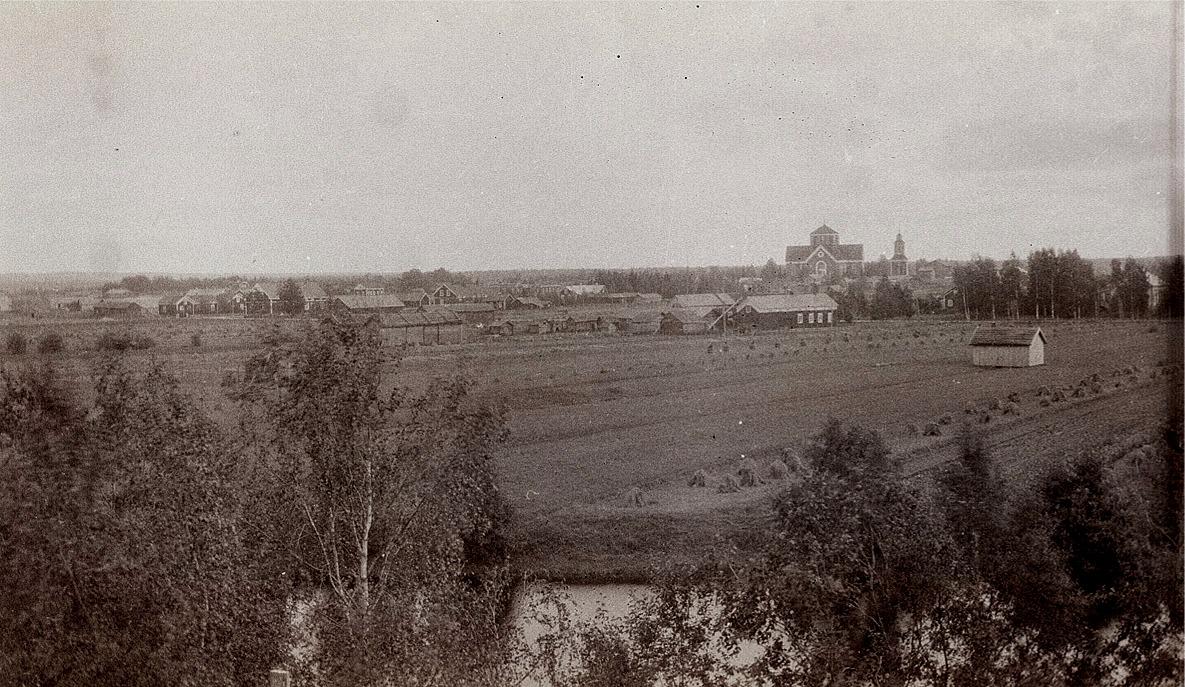 Fotografi taget från norra sidan mot kyrkan. Framför kyrkan Lillmangs gård med de 4 fönstren och till höger