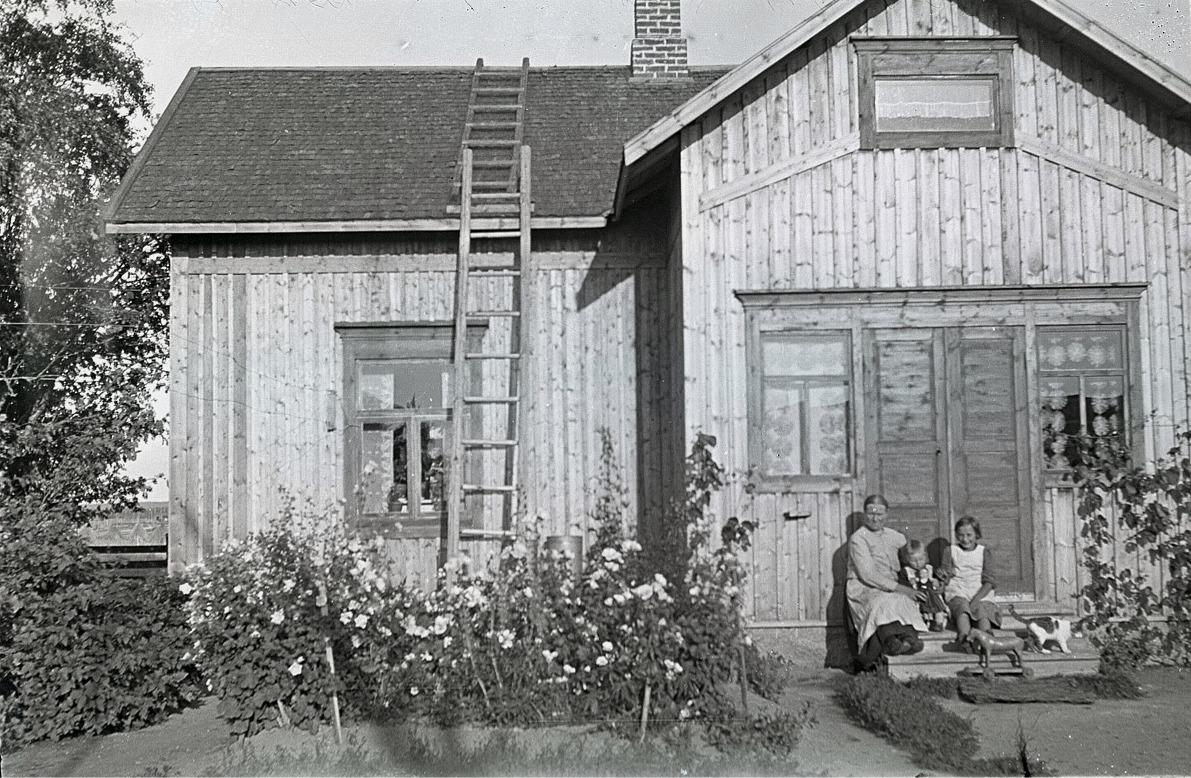 Alvina Björses sitter på brotrappan där hemma tillsammans med 2 barnbarn, en katt och en trähäst som går på hjul.