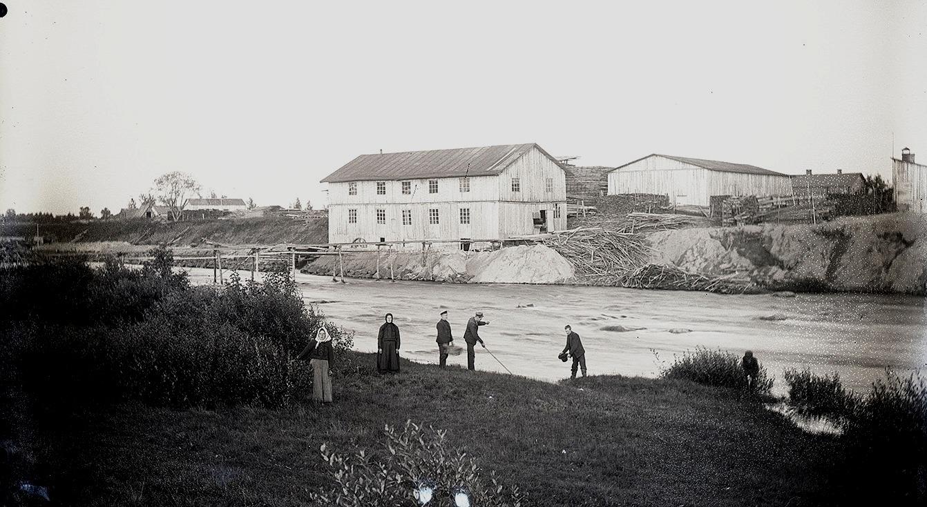 På andra sidan ån ser vi Viktor Nylunds såg- och snickeribyggnad som han byggde i början på 1900-talet. Byggnaden förstördes i en brand år 1914 och han byggde då en ny sågbyggnad på samma ställe.