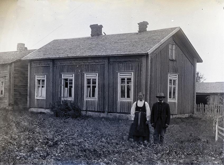 Här står Klemets Emil och Manda framför gården medan den ännu stod uppe i centrum lite öster om folkskolan. Fotot från ca 1915 och gården flyttades sedan ner till Klemetsändan där den skarvades i med en vinkel.