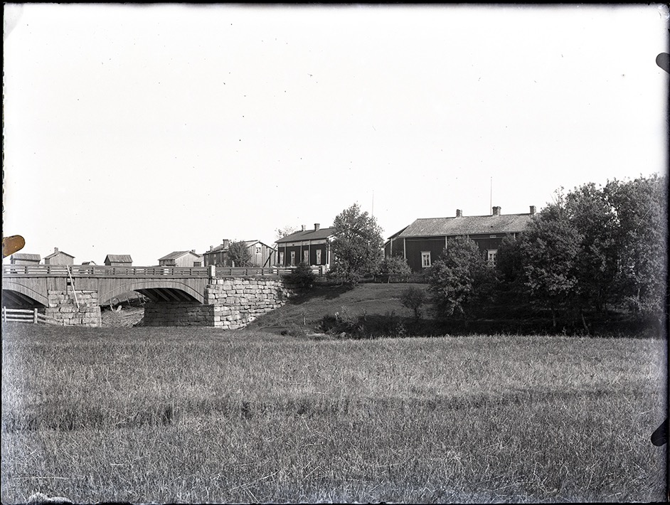 """På det här fotot från ca 1915 ser vi hur den gamla gården på Åddin såg ut. Huset mitt i bild är """"Kork""""-Frans Eklund gård som den såg ut före den byggdes på med en våning till. Följande gård är högst troligt den första gården som Långarna byggde på Brobackan i början på 1800-talet. Storbron till vänster byggdes 1855 och här ser vi hur brolocket i trä såg ut."""