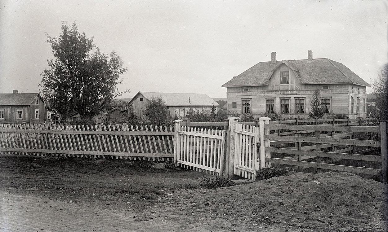 """Till höger Viktor Klemets ståtliga bondgård """"där Bränninas"""". Den stod lite öster om folkskolan och den revs bara för några år sedan. Genom den mindre grinden, som kallades """"lillgrinden"""" kom man ner till skolan."""