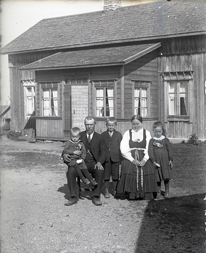 Här sitter skräddaren Viktor Söderqvist (1883-1954) med sonen Yngve (1920-2005) i famnen. Mitt i bild står Valter Söderqvist (1916-2005) bredvid mor Amanda (f. Söderholm 1888-1959). Till höger står Ellen (1918-2010) senare gift Sten. Yngsta dottern Elvi (1926-1968) senare gift Hagback, fattas på bilden.