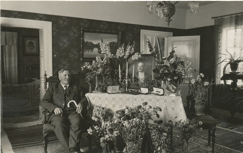 Här sitter Viktor Nylund bredvid bordet fyllt med fina blommor och presenter på sin 60-årsdag år 1933. På bordet står president Svinhufvuds porträtt.