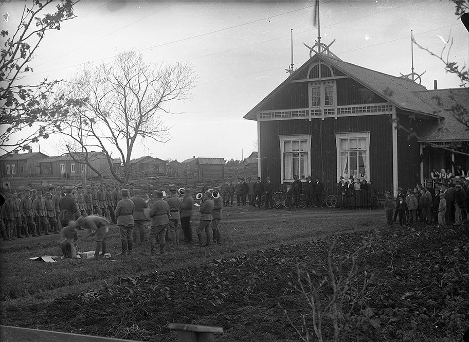 Skyddskårister uppställda på ungdomsföreningens gårdsplan. Till höger föreningshuset Majbo som invigdes 1910. Notera den stora mängden byggnader tillvänster uppe på Byåsen.