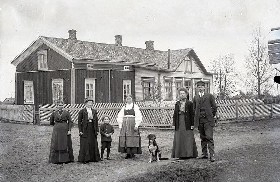 Fina gäster uppställda utanför Nylunds gård på Sunnantillvägen. Ida klädd i folkdräkt med lilla Rurik bredvid sig.