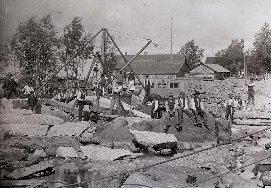 Med taljor och block lyfter stenhuggarna de tunga stenarna på plats då dammen till kraftverket byggdes ca 1916. Den unga pojken som står inne i en stenkista långt till vänster är Rurik Nylund, född 1907.