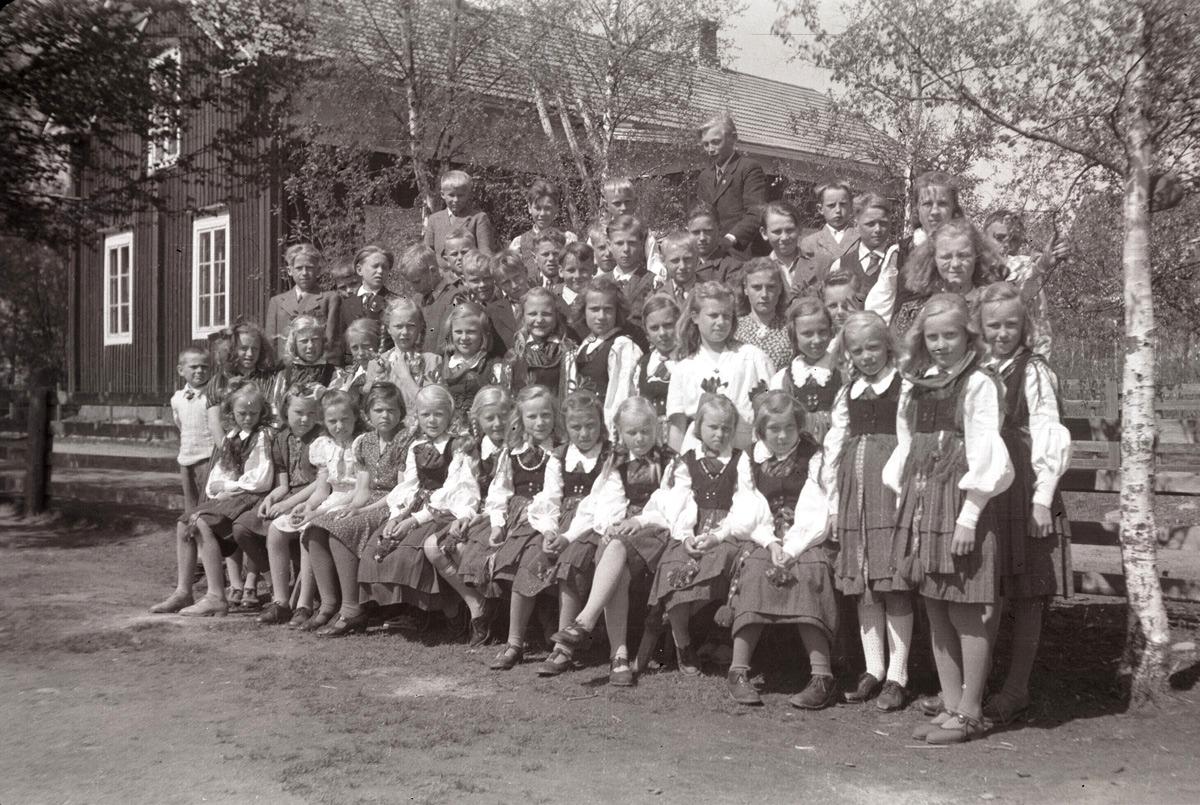 Flera flickor iklädda folkdräkt vid skolavslutningen 1947.