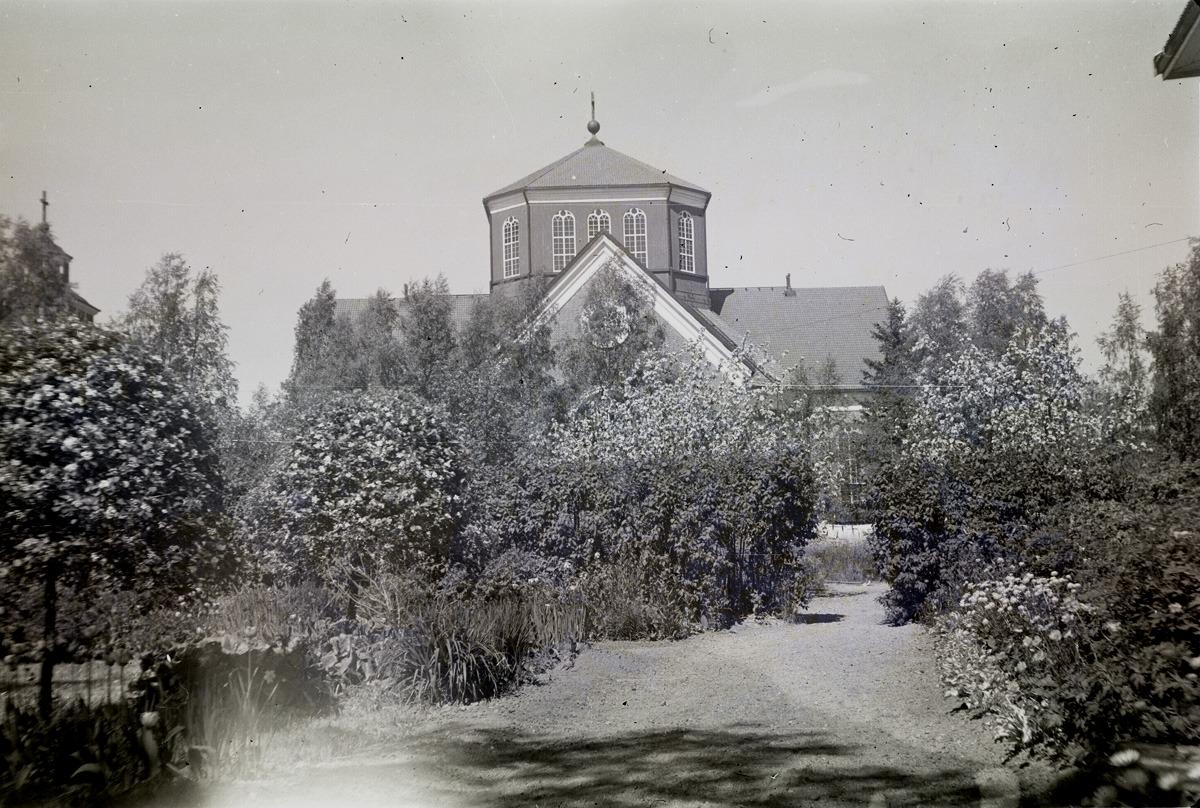 Så gott som varje år fotograferade Selim Björses sin trädgård vid södra folkskolan och här lyckades han få ett fint foto av kyrkan också.