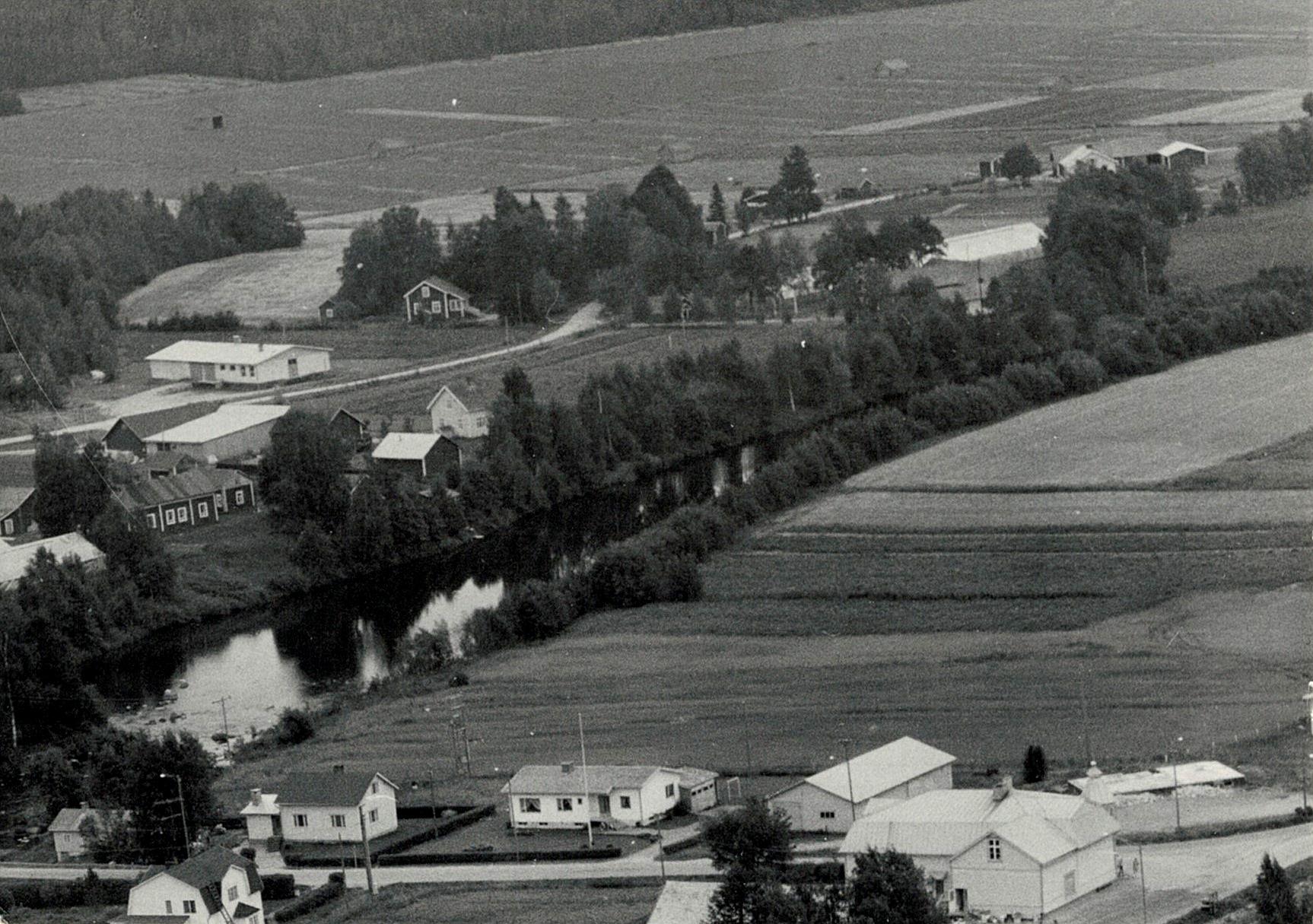 På flygfotot från 1972 syns Backlundas gamla gård till vänster på A-sidon. Bakom gården syns Lappfjärds Potatis förpackningshall som byggdes 1965 och till höger om den Nylundas-Idas lillstuga. Längst nere till höger syns husgrunden till det nedbrunna sparbankshuset.