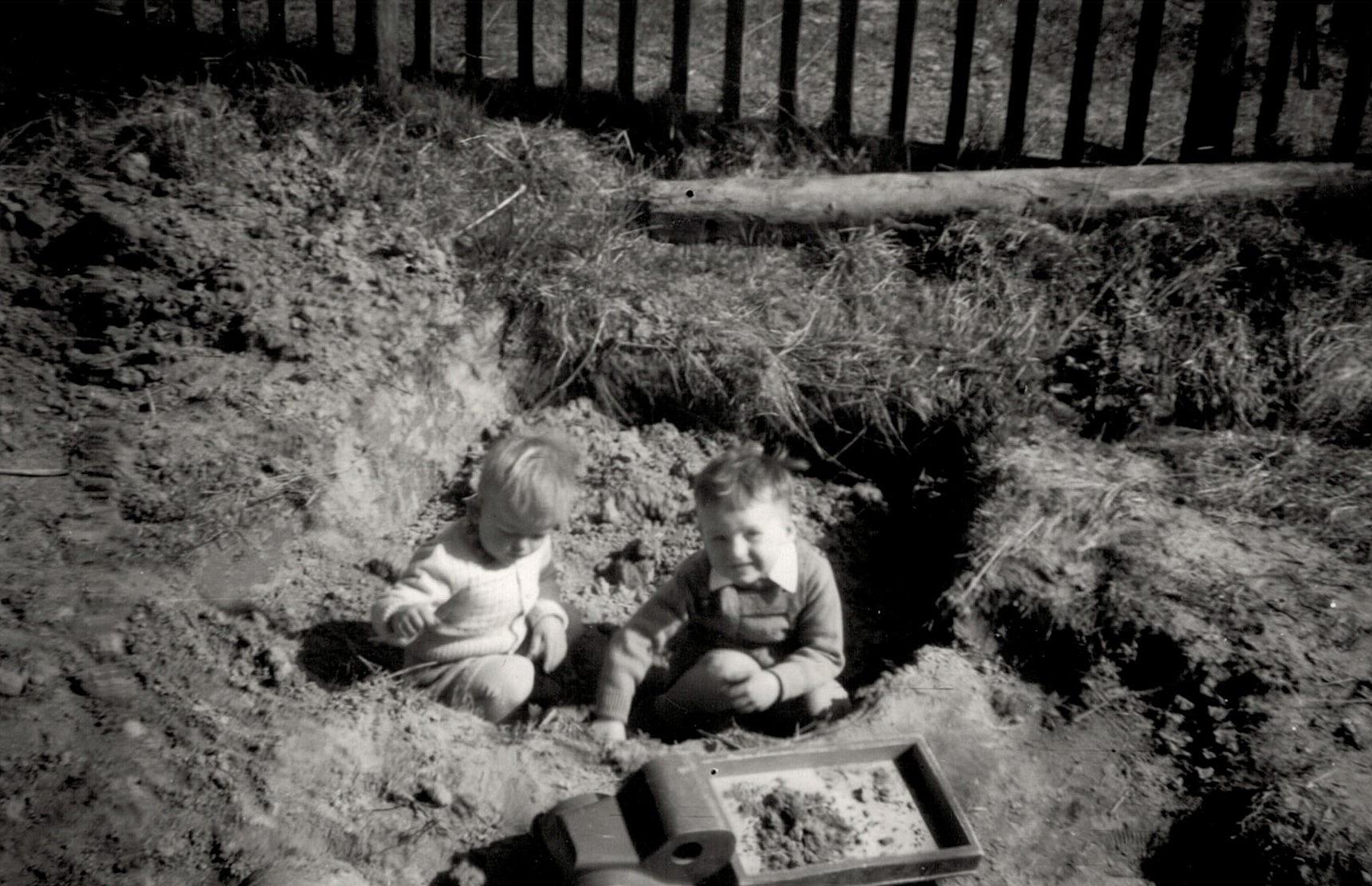 """John och Kurt leker ovanpå den nyss uppgrävda """"dyngbrånnin"""" som fanns precis utanför köksfönstret. Fotot från ca 1956."""