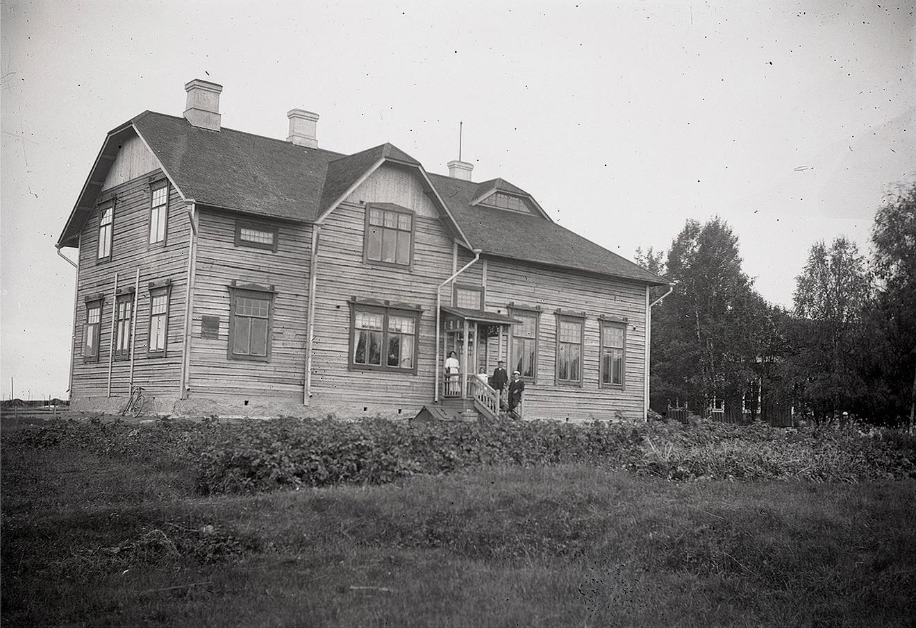 Här den splitternya skolan fotograferad år 1909, där några av lärare Wadströms barn stående på vindstrappan. Till höger skymtar den gamla skolan som revs följande år, då en del av virket kunde användas för byggandet av folkskolan i Perus. Foto Viktor Nylund.