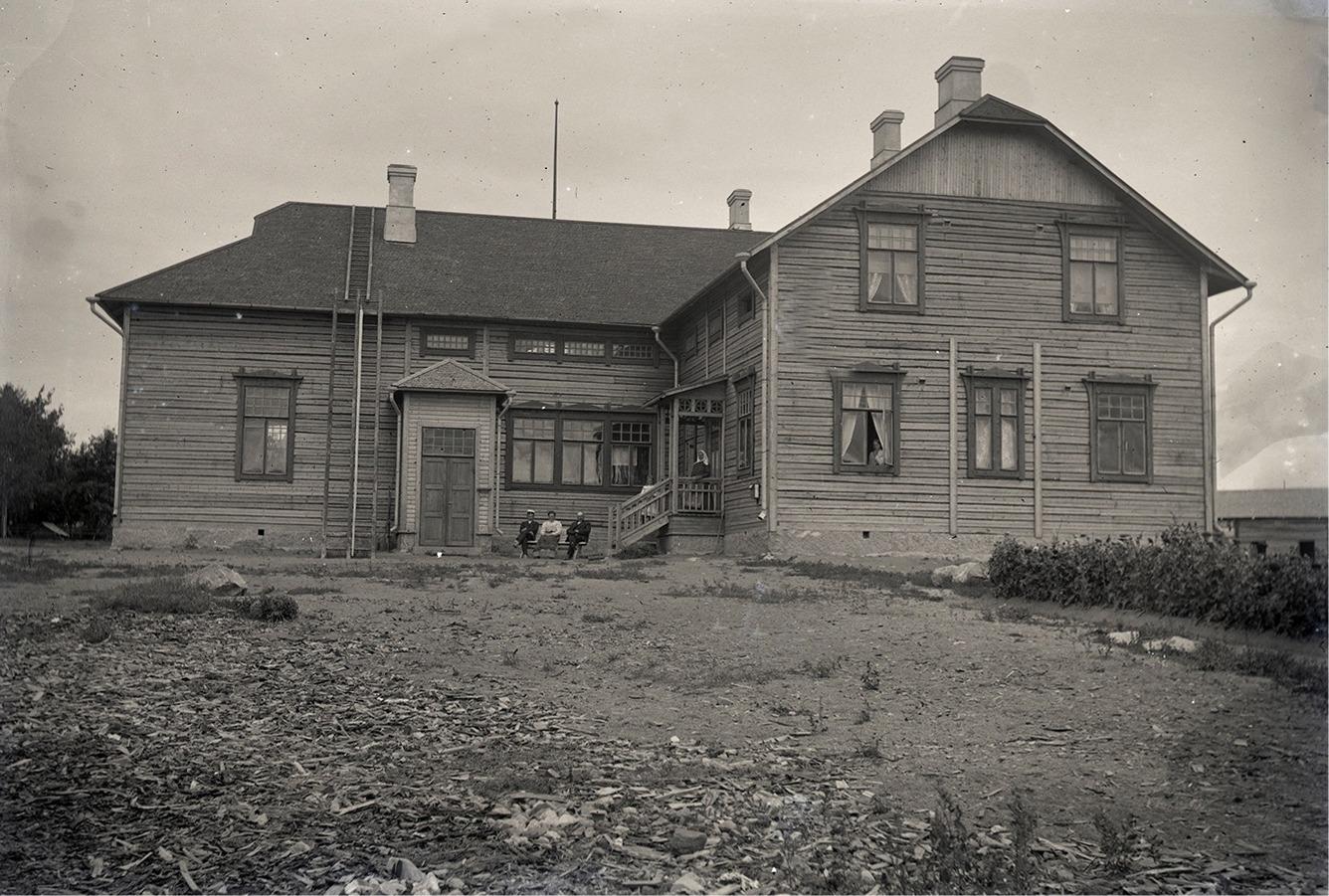 En del av lärarfamiljen Wadström utanför det nya skolhuset, där spånorna fortfarande ligger på skolgården.