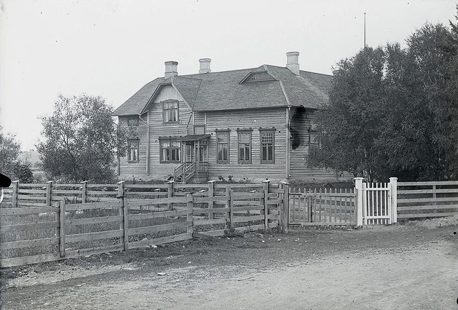 """Folkskolan fotograferad från norr, där """"lillgrinden"""" leder ner till skolan och den större grinden """"ner ti Bränninas"""" alltså till Klemets gård."""