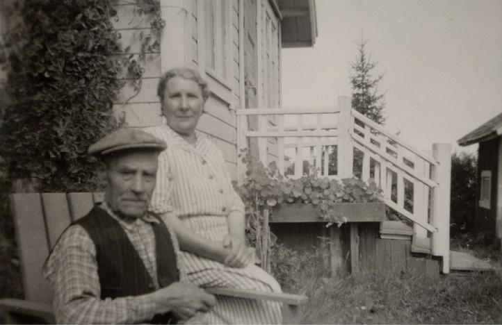 """Här sitter """"Brännin"""" själv, alltså Erik Anders Klemets tillsammans med hustrun Alvina, framför lillstugan där de bodde på gamla dar."""
