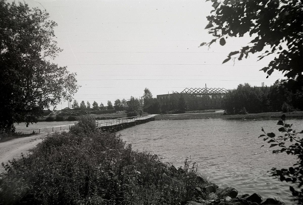 """Ungdomslokalen under byggnadsskedet 1950 fotograferad från andra sidan ån. """"Gamälbroen"""" leder över till den andra sidan."""