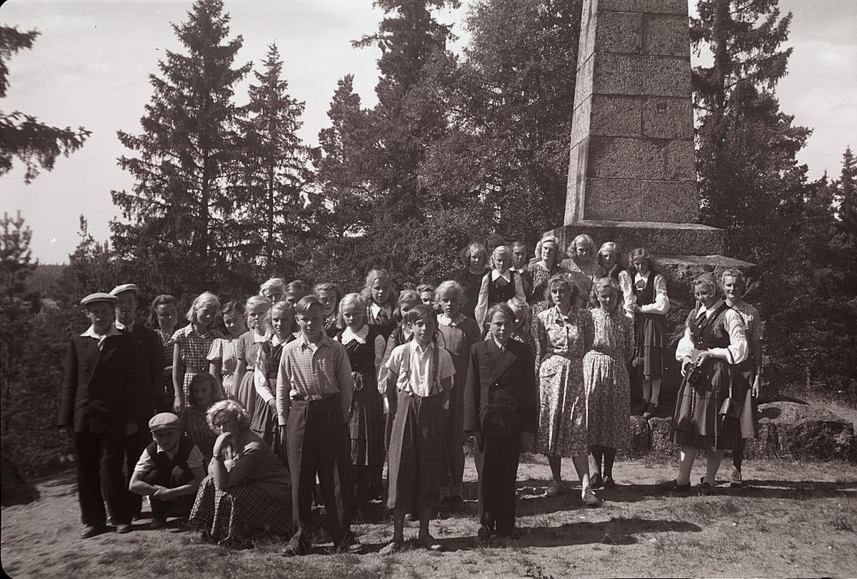 Lantbruksklubbens medlemmar framför minnesstenen över de stupade i Finska kriget 1808-09, som finns i Oravais. Fotot från 1950.