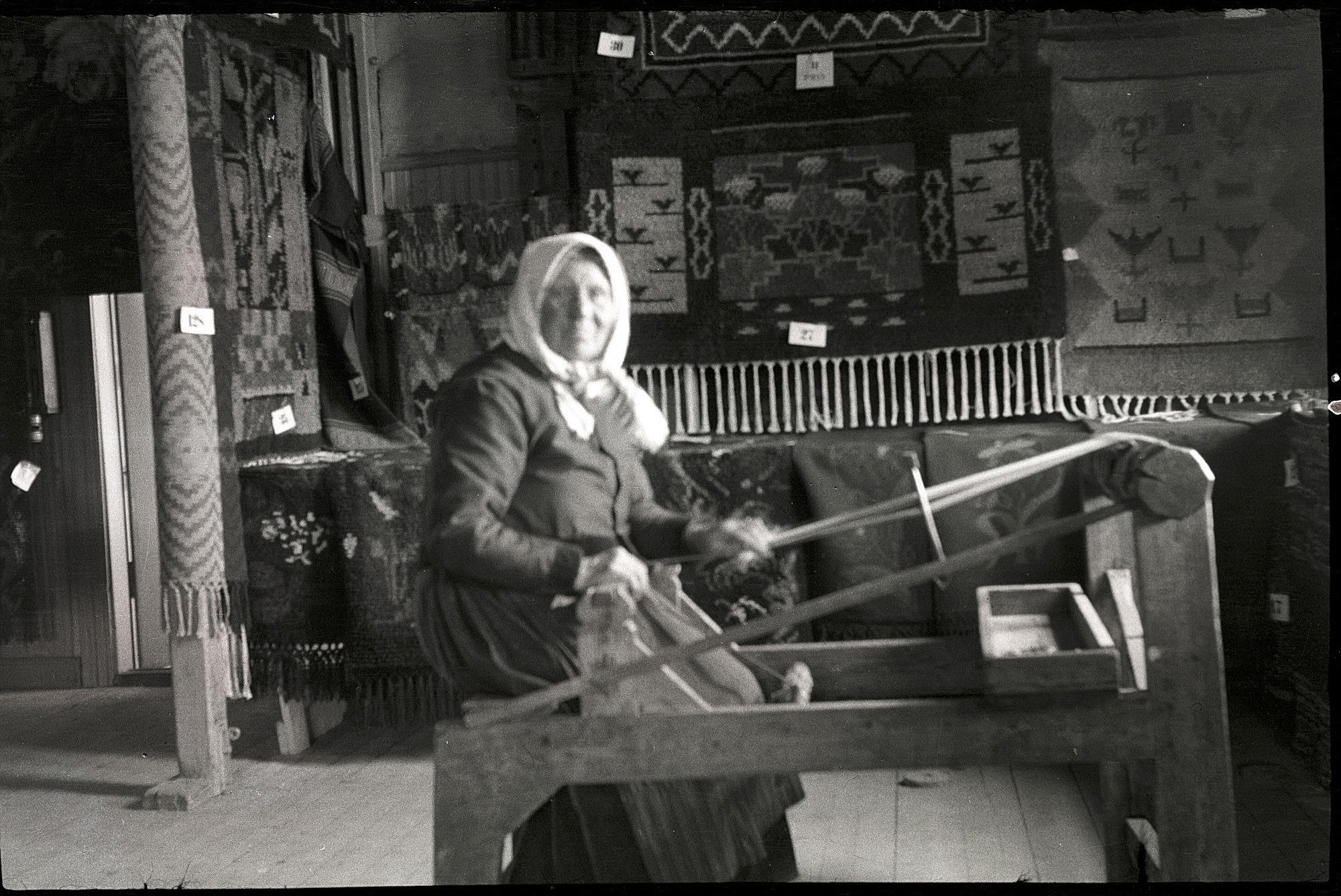 Bleckslagar-Manda visar hur det går till att väva förklädesband på lantbruksutställningen i Lappfjärd 1938. Runt omkring henne finns flera fina vävnader utställda. Foto Selim Björses, SLS:s arkiv.