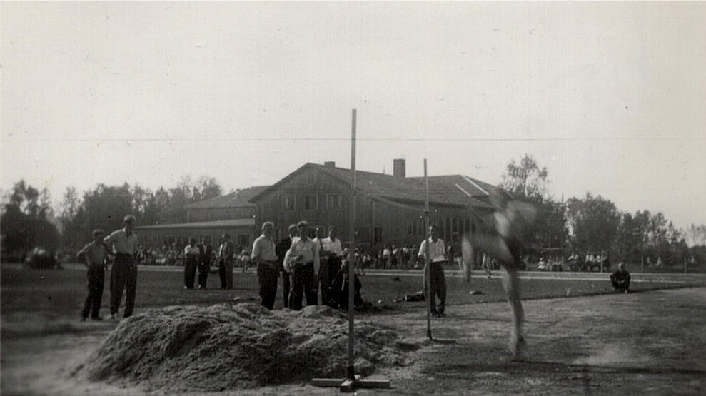 En höjdhoppare tar sats för att hoppa över ribban, för att sedan landa i spånhopen. I bakgrunden den ännu omålade ungdomslokalen. Fotot från invigningen av den nya sportplanen 21.8.1955.