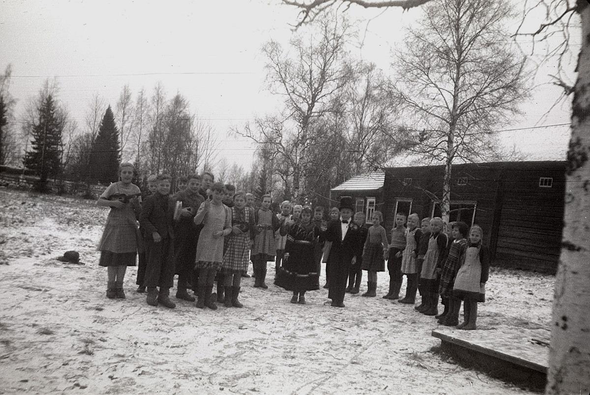 """Här på skolgården övas det inför julfesten 1953, då brudparet Solveig Lärka och Torolf Söderlund skall framföra ett riktigt lappfjärdsbröllop. Orkestern är med, liksom """"pellhaldaren"""" och gästerna. I bakgrunden skolans bastu och lider."""