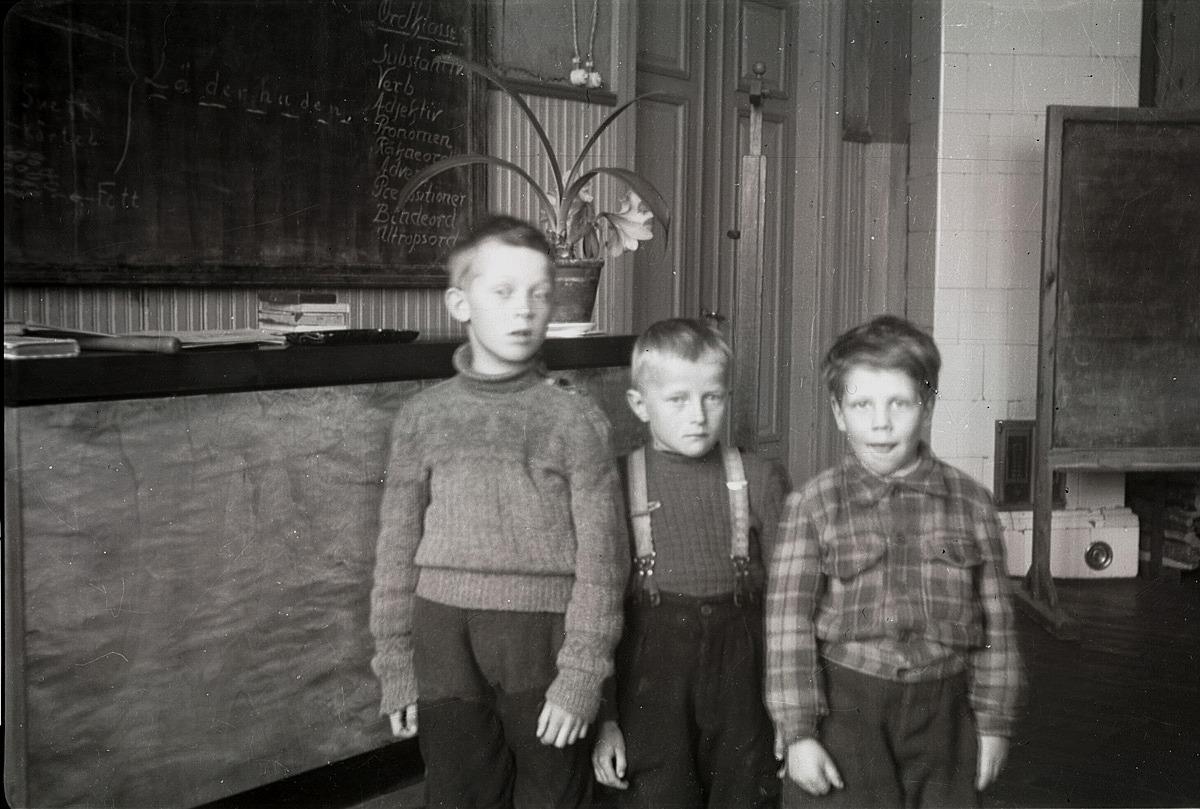 Enligt texten på svarta tavlan har just varit grammatiklektion på södra folkskolan. Pojken till vänster är okänd men i mitten står Börje Norrholm och till höger Håkan Björses.