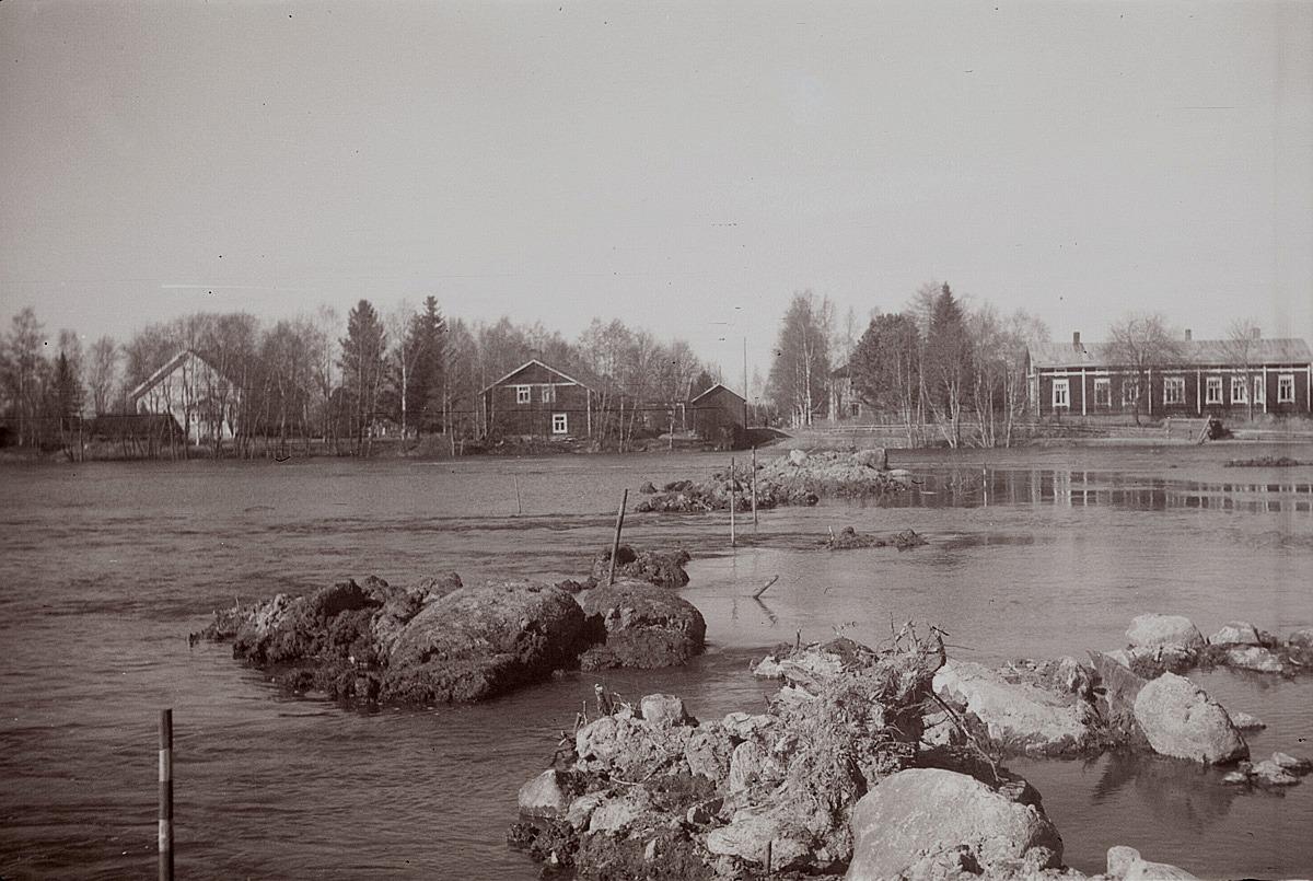 Vårfloden i Lappfjärds å 1956. Till vänster Helsingforsbanken, i mitten garvare Stenmans gård och till höger lantmätare Molanders gård. Den kommande brobanken till Centralbron är utstakad i ån.